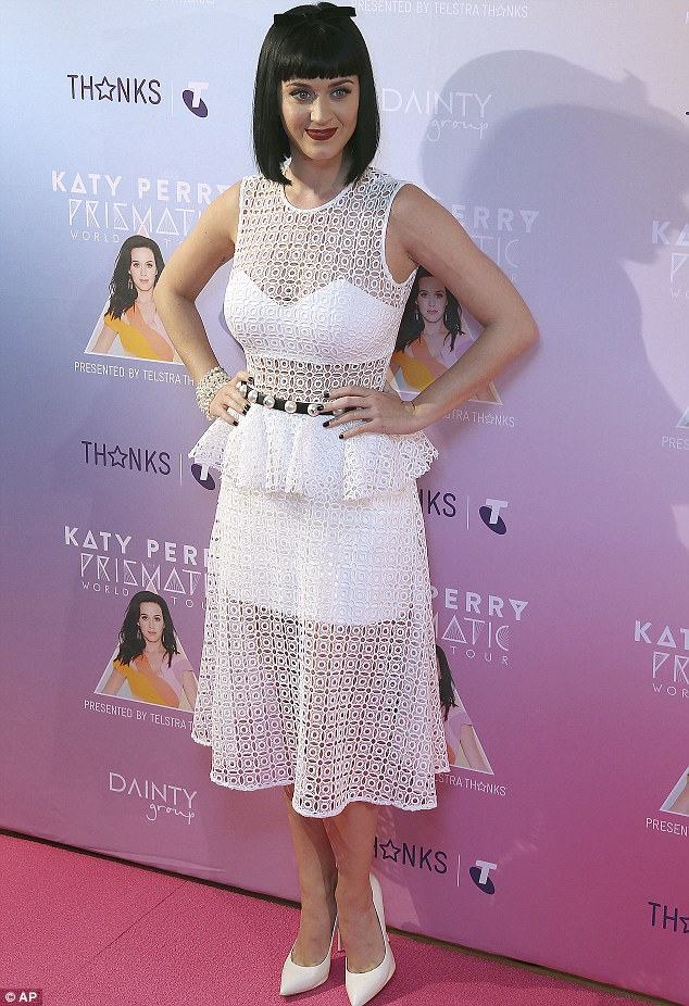 What a transformation! Katy Perry looked more like her usual self in a pretty white dress and heels at an appearance at the Telstra store in the Sydney CBD on Tuesday