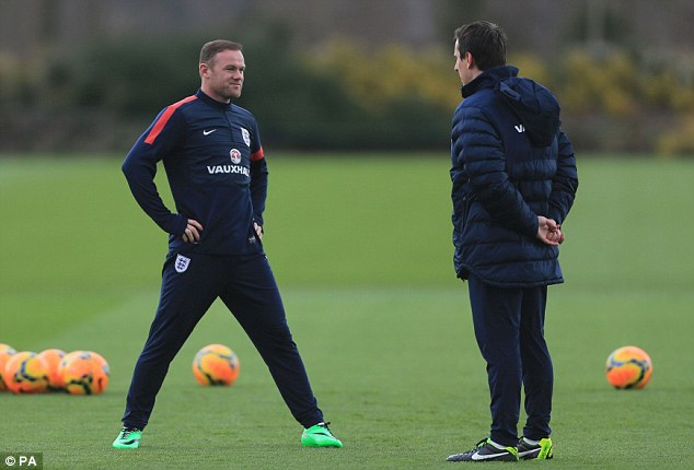 Talking tactics: England forward Wayne Rooney (left) chats to Gary Neville (right) at training