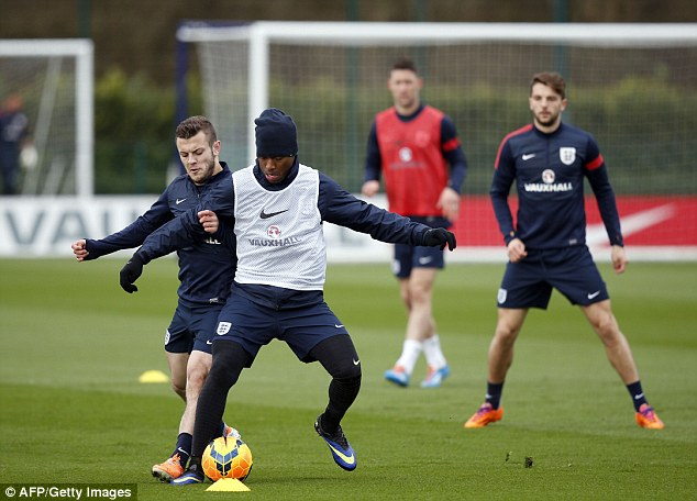 Tight marking: Wilshere (left) vies for the ball against Daniel Sturridge (right) at England training on Monday