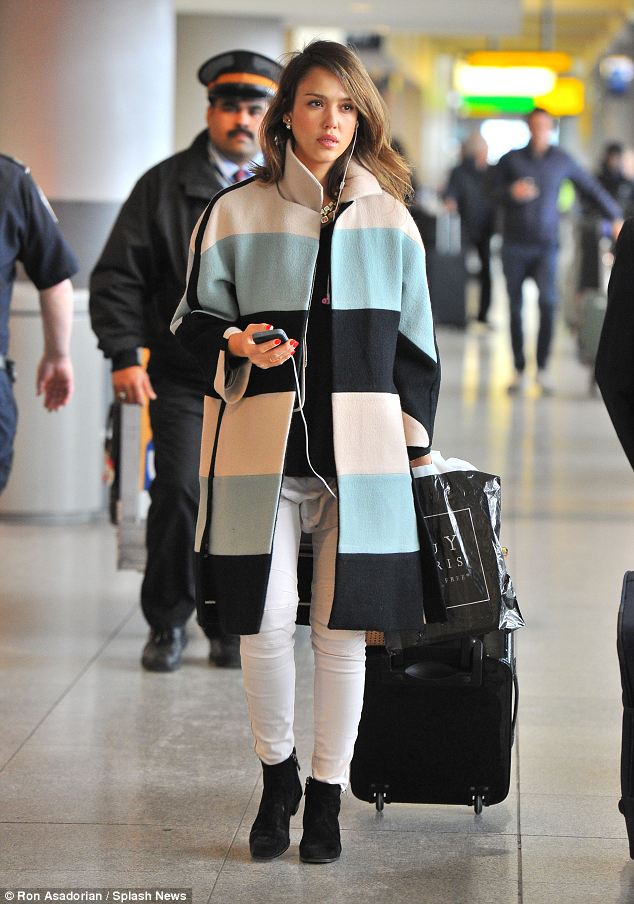 Casual chic: Jessica Alba was stylish on her travels as she arrived at JFK airport wearing a colourful striped coat