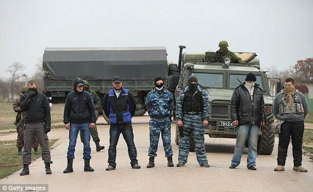 Unimpressed: A group of mostly-masked pro-Russian militants arrived at the air base shortly after the stand-off, as Russian-led troops blockade Ukrainian military bases