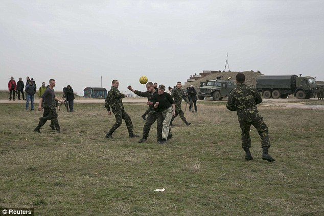 Down time: Ukrainian serviceman play soccer near Russian military vehicles at Belbek airport in the Crimea region