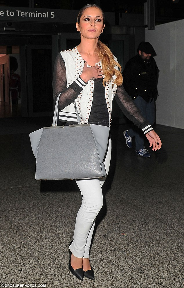 Looking sharp: The singer wore a black and white suit with heels as she arrived back in London