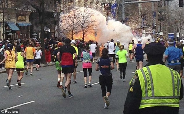 Terror: Runners continue to run towards the finish line of the Boston Marathon as an explosion erupts near the finish line of the race
