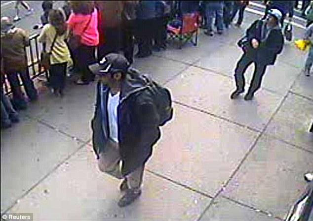 Suspects: Tamerlan and Dzhokhar Tsarnaev walk around the finishing line of the Boston marathon on April 15