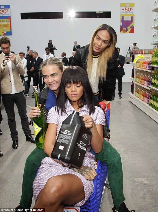 Fashion fun: Prentending to drink out of faux bottles of alcohol that were lining the shelves of the catwalk turned supermarket, the girls seemed to be having a whale of a time as the indulged in a supermodel sweep of sorts