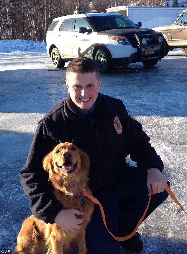 Alaska State Troopers Lucas Hegg poses with Amber the 2-year-old golden retriever who saved his owner's life by keeping him warm and alerting passersby