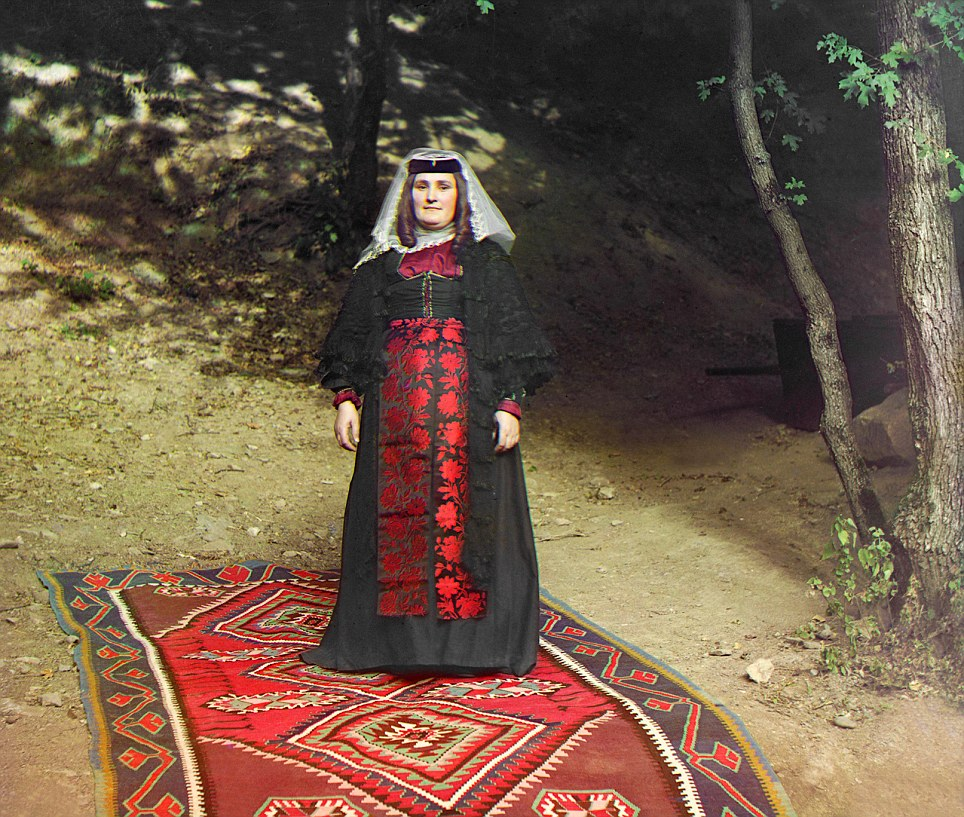 A wealthy woman poses outdoors on a magnificent rug in a richly ornamented outfit and headdress