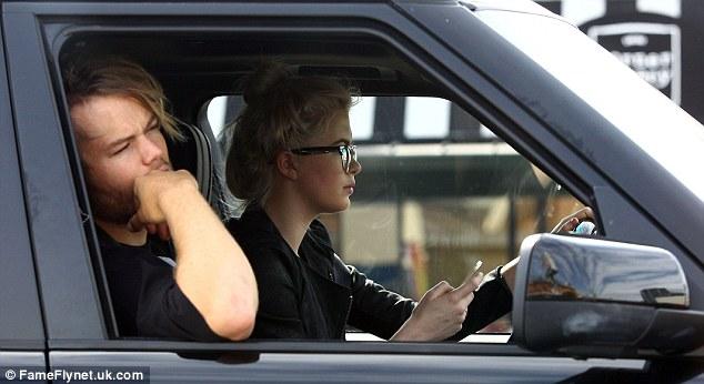 Eyes on the road: Ireland was seen looking at her phone before they set off