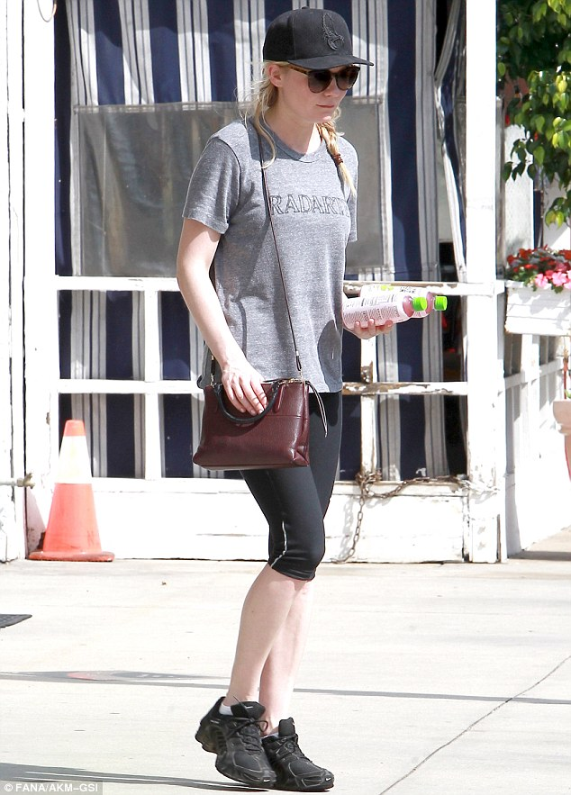Feeling refreshed: The US star clutched two drinks as she left the venue while sporting a black cap