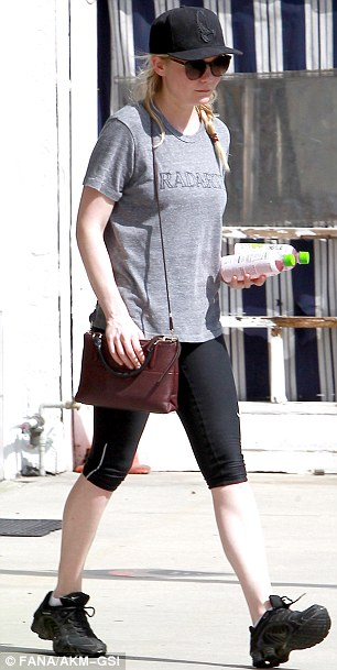 Striding out: However Kirsten teamed her outfit with a chic and ladylike burgundy handbag