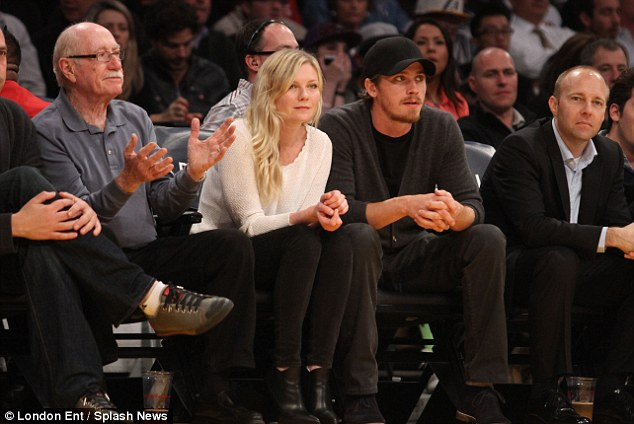 Action-packed: The actress kept her eyes on the game as she enjoyed an evening out with her man at California's Staples Centre