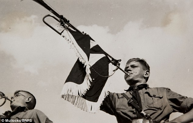 A member of the Hitler Youth pictured blowing a bugle