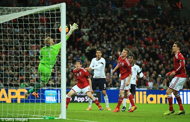 Ball watching: England and Denmark players look on as the ball escapes Kasper Schmeichel's clutches