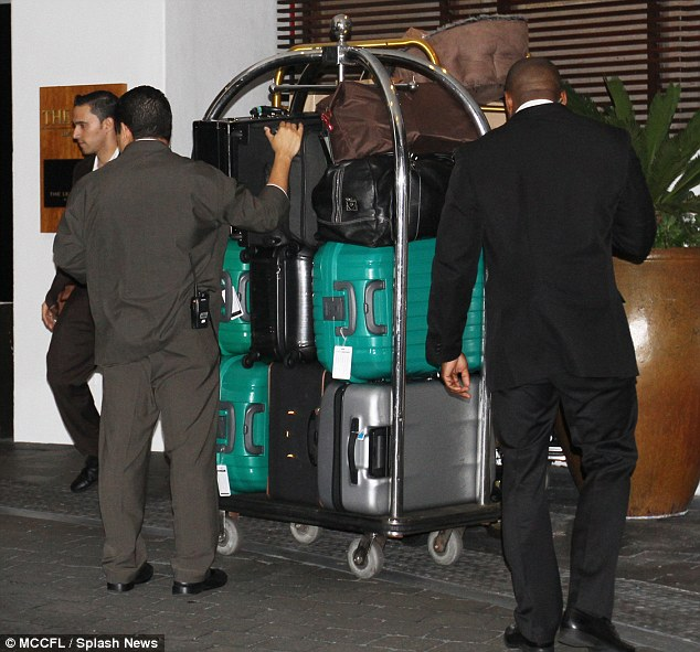 Loaded up: The hotel porters were also seen wheeling out a trolley full of suitcases