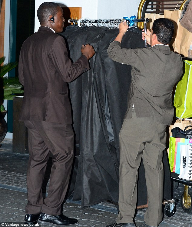 Clothing for every occasion: A clothes rack full of items in black clothes bags was also seen being wheeled to the car
