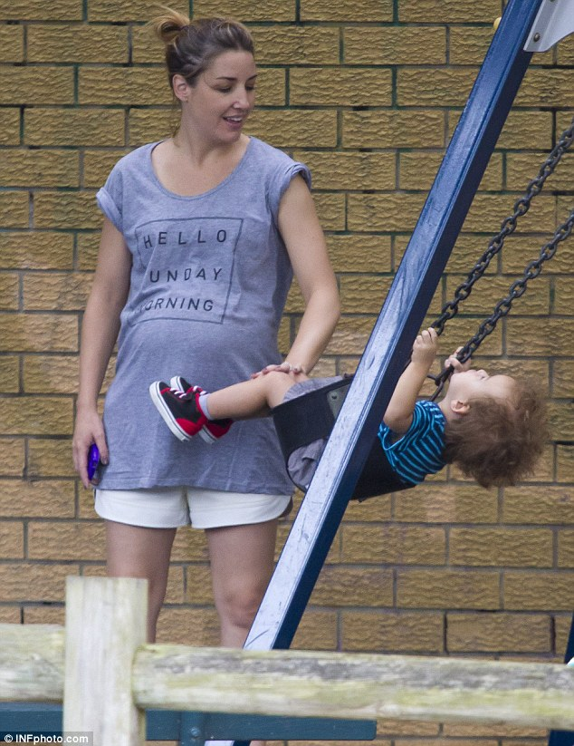 Keeping close: She kept a close eye on the toddler as he gained momentum on the swing