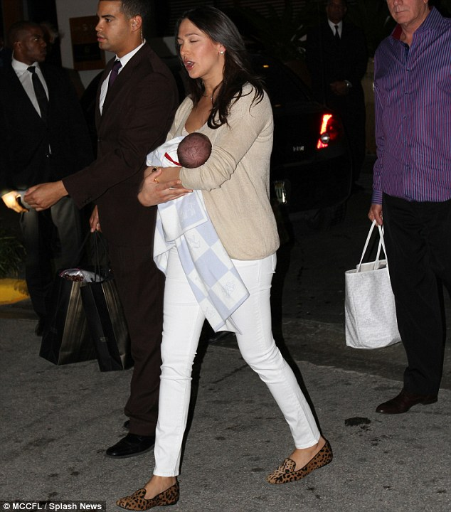 Precious cargo: Lauren looked chic in a white and nude outfit as she toted baby Eric to the car