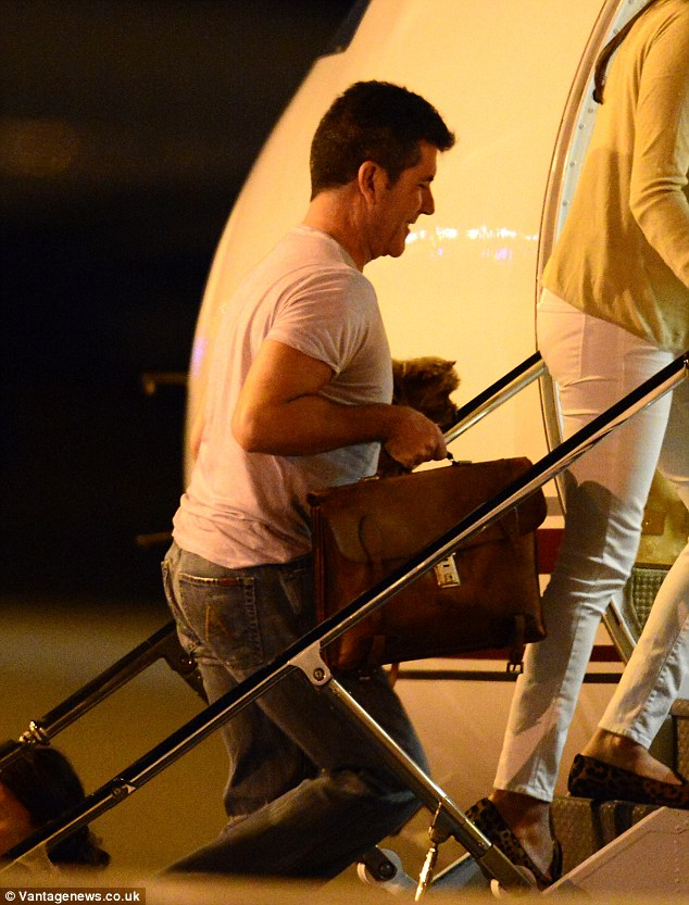 It's a dog's life: Simon carries his beloved puppy onto the private jet