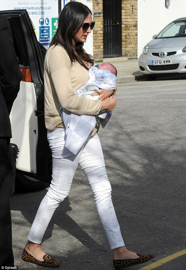 Home time: Lauren Silverman cradled baby Eric as they arrived back at Simon Cowell's London mansion on Thursday