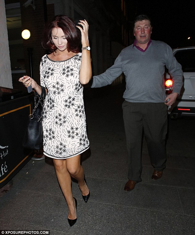 Loving: Her dad put a protective arm around her as they made their way to the popular venue