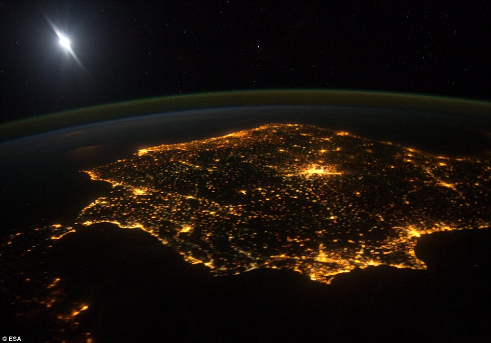 This image from the International Space Station shows the Iberian Peninsula including Spain and Portugal at night. The lights from human settlements reveal where the major towns and activity are. The large mass of light in the middle is Madrid, Spain's capital city. The Iberian coastline is heavily populated with Valencia and Barcelona along the Mediterranean Sea prominent at the bottom right of this photo. The white light in the top left of the photo is a reflection of the camera flash