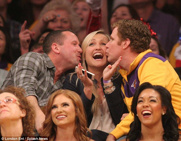 Three's a crowd: The mystery blonde and the Lakers fans both found it hilarious that she was being kissed by the movie star