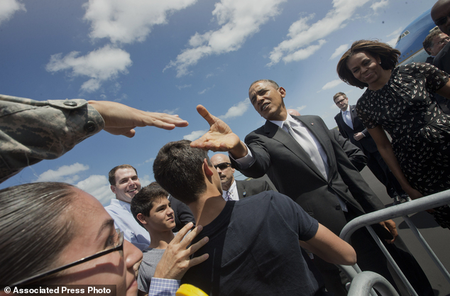 Touching down: President Barack Obama and First Lady Michelle Obama greet members of the military on the tarmac upon their arrival at Homestead Air Reserve Base, Friday, March 7, 2014, in Homestead, Florida