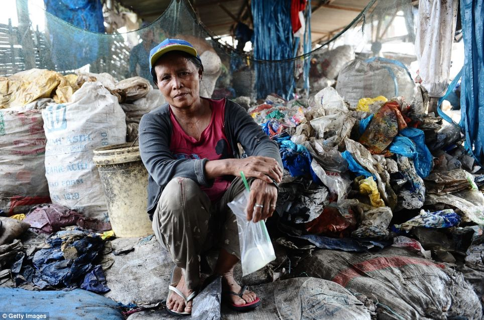 The women rifle through and scavenge garbage from the landfill at Benowo in Surabaya, Indonesia, every day to earn money to feed themselves and their families