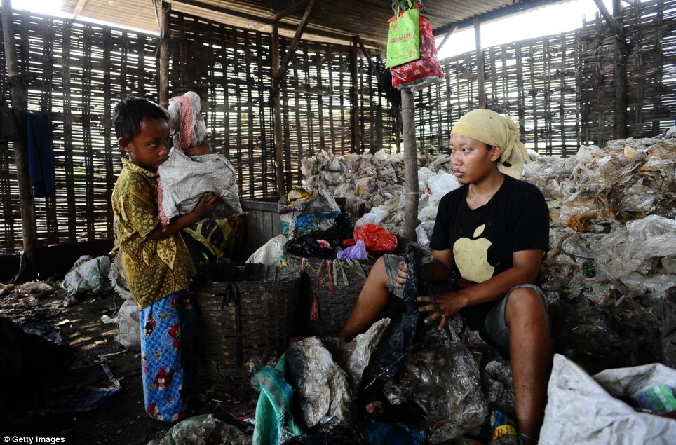 Dozens of women, often accompanied by their young children, rifle through rubbish every day at the Indonesian landfill site to earn £1.20 a day
