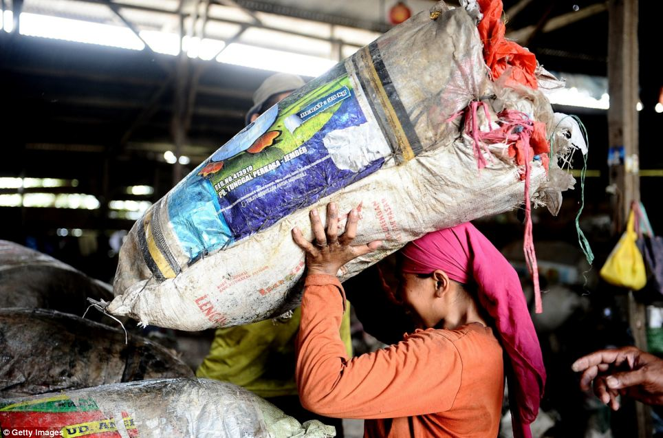A woman lifts a large sack of rubbish at the Benowo landfill site in Surabaya, Indonesia, on March 7. Almost all of the rubbish from across the city ends up at the site