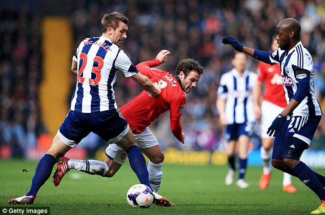 Stopped in his tracks: United midfielder Juan Mata is tackled by West Brom's Gareth McAuley, left, as team-mate Youssuf Mulumbu looks on