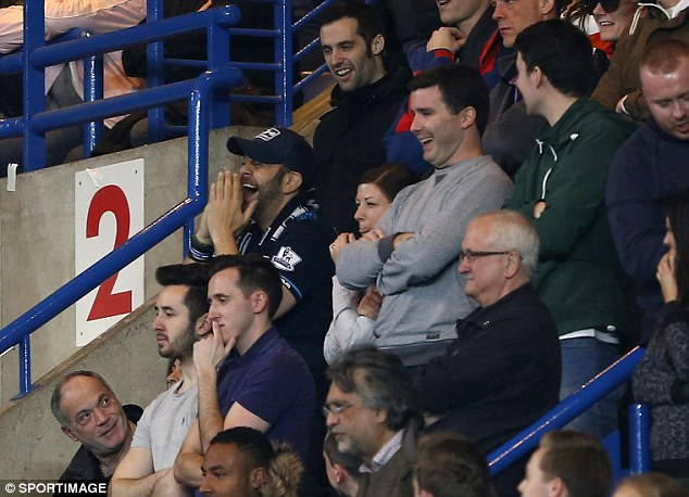 All smiles: Man vs Food presenter Adam Richman (blue cap) sits in the Tottenham fans