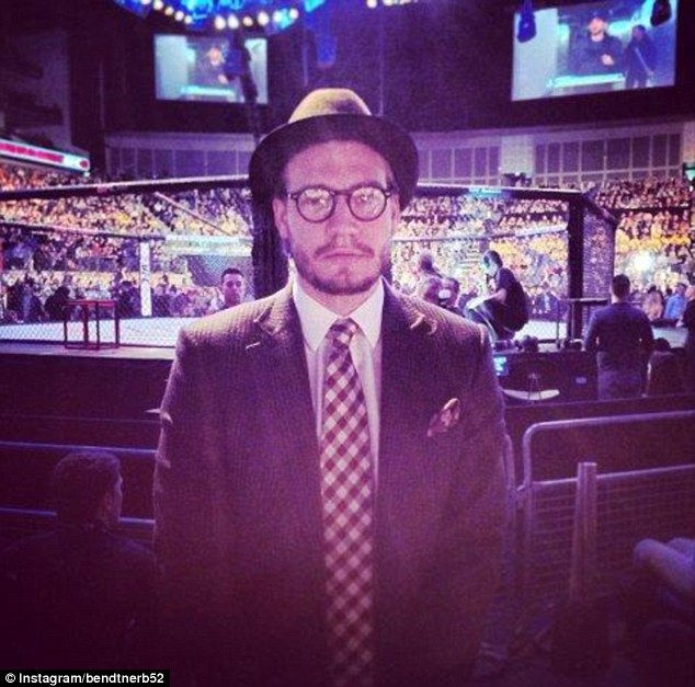 Fetching: Nicklas Bendtner, wearing a suit, pocket square, chequered tie, pork pie hat and round spectacles, led a contingent of Arsenal players at the UFC Fight Night at the O2 Arena in London