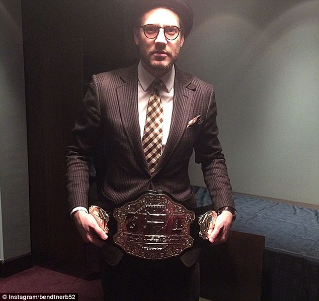 The champ: Bendtner poses with a replica UFC belt as he and his team-mates take in the action at the O2 Arena