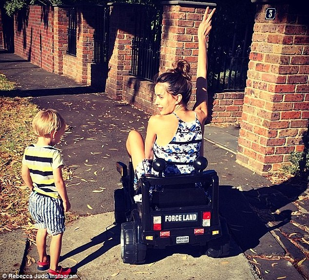 Stealing her son's ride: Rebecca Judd shared a picture of herself racing around on her son's toy car