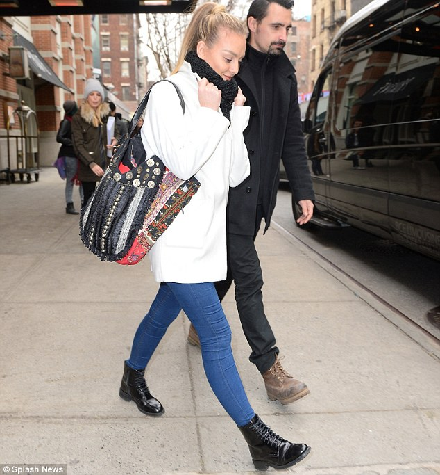 Sidewalk strut: It was hard to miss the blonde beauty's  large tote bag which featured various colours and prints