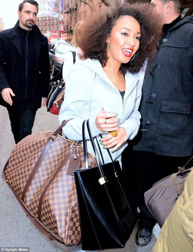 Bag lady: The 22-year-old sported a large Afro 'do and red lipstick after meeting with fans