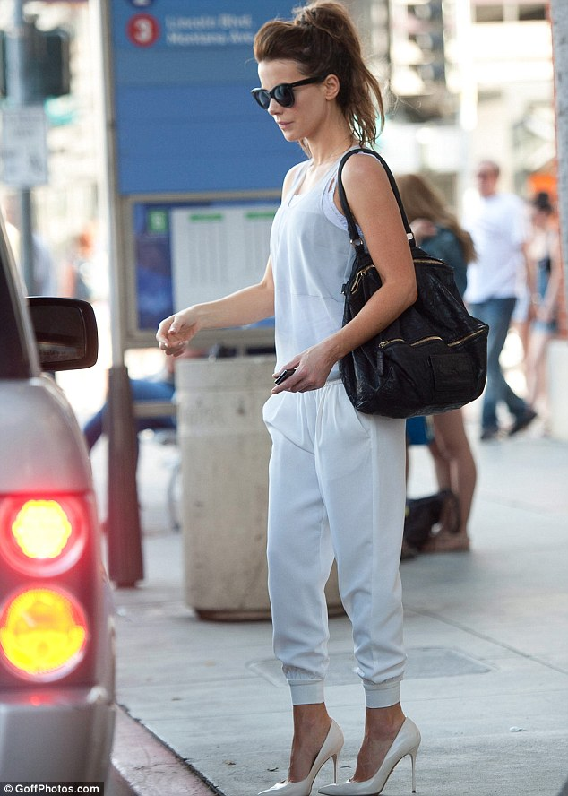 Fashion forward: The British beauty wore an unusual pair of white trousers that were pleated at the waist and cuffed at her ankles along with a white lace camisole covered by a light vest