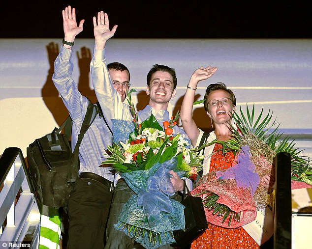 reunited: Shane Bauer, Josh Fattal and Sarah Shourd wave in delight while boarding a flight back to the U.S. in September 2011