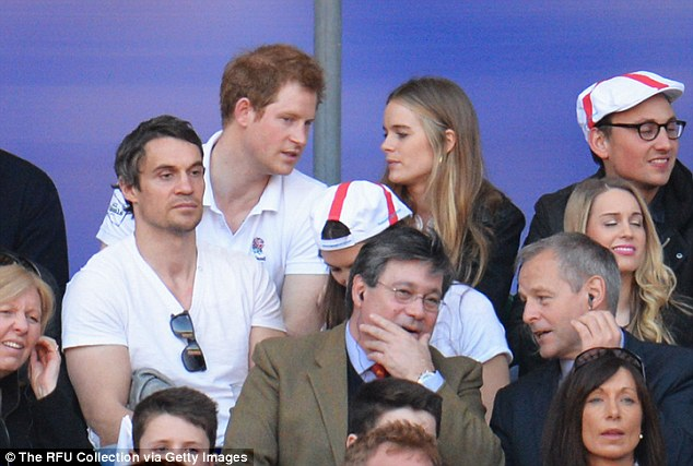 Prince Harry talks to Cressida without taking his eyes off the RBS Six Nations match between England and Wales at Twickenham Stadium on Saturday