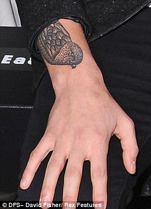 Extensive collection: Louis already has a vast array of tattoos, including a random collection on his right arm and a large bird design on his forearm
