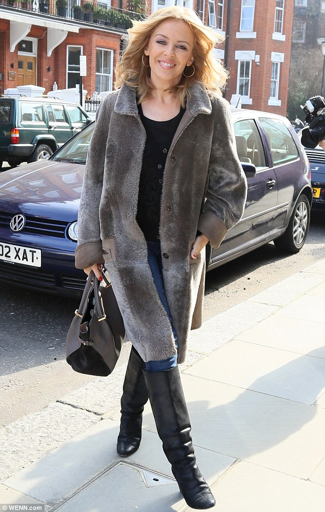 Lovely: Kylie Minogue makes her way into a London studio for an appearance on MTV Asks on Monday morning