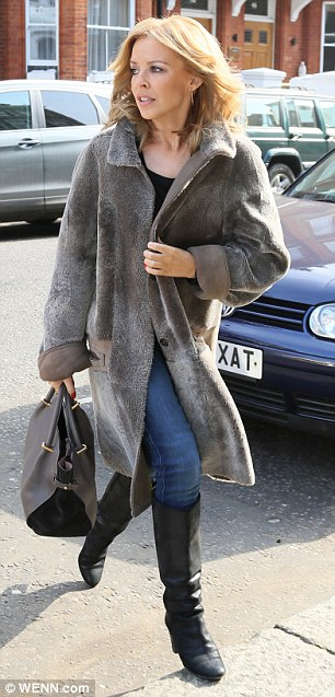 Smart casual: Kylie opted for a simple black top and skinny jeans with knee-length boots and a collared grey coat for her latest appearance in London on Monday