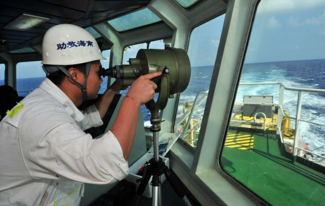 A member of a Chinese emergency response team adjusts equipment on the rescue vessel 'South China Sea Rescue 101', on the way to search for the missing plane