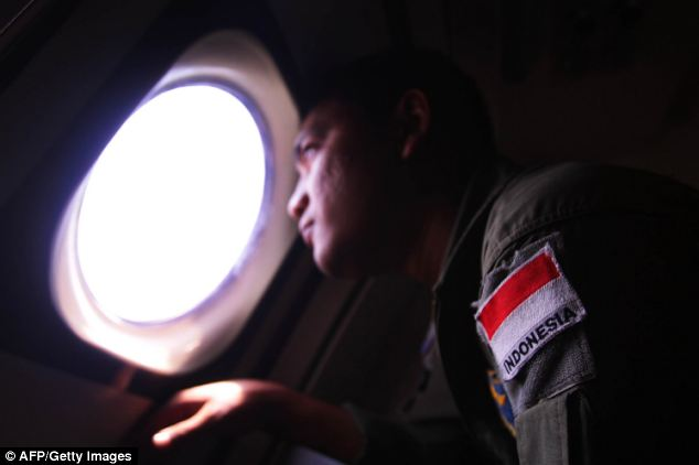 An Indonesian Navy search and rescue personel looks out from the aircraft window during an aerial search for the missing plane