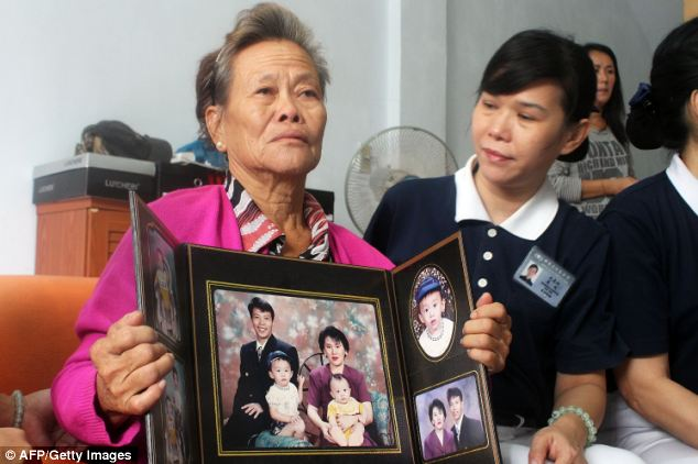 Grieving Indonesian mother Suharni displays a portrait of her son Sugianto Lo and wife Vinny Chynthya who are both passengers of the missing Malaysia Airlines flight