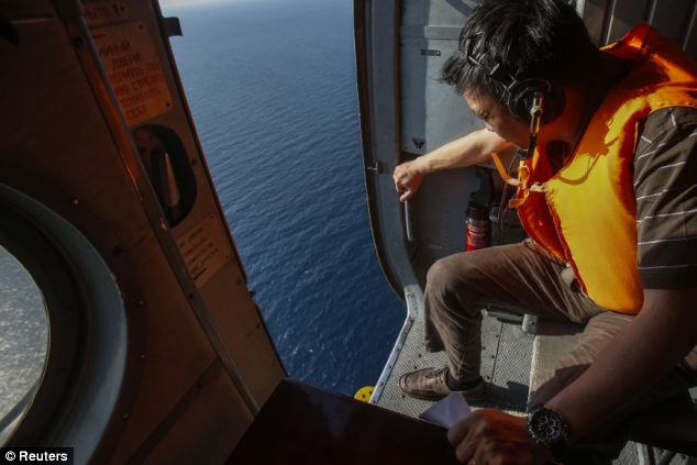 An officer looks out of a helicopter during a mission to find the Malaysia Airlines flight MH370