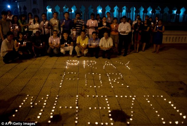 A group of Malaysian residents pose after lighting candles during a vigil for missing Malaysia Airlines passengers at the Independence Square in Kuala Lumpur