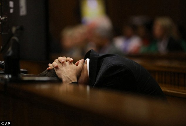 Too much to bear: Pistorius covers his head as he listens to details about his girlfriend's death